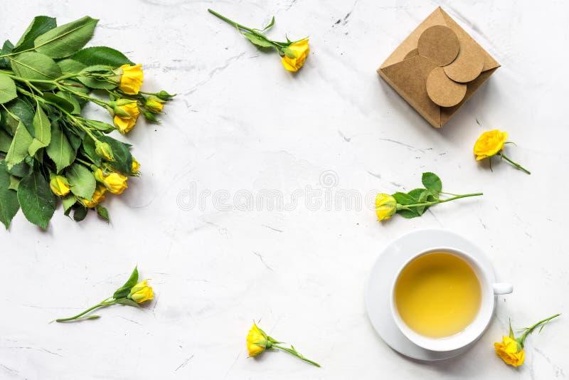Lebensstilkonzept mit Tee und Rosen auf Haupttischplattenansichtmodell lizenzfreie stockbilder