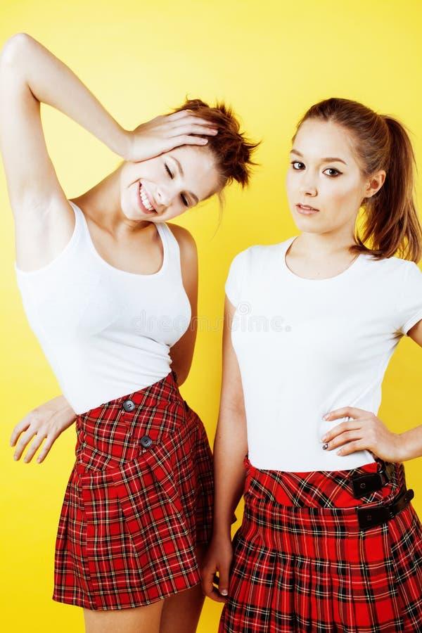 Lebensstilleutekonzept: hübsches Mädchen der Schule zwei, das Spaß auf gelbem Hintergrund, glückliche lächelnde Studenten hat stockbild