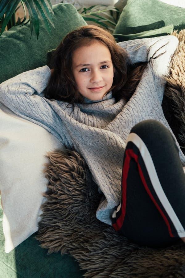 Lebensstilmodeporträt des jungen stilvollen Hippie-Kindermädchens, das nahe Sofa, die tragende nette modische Ausstattung sitzt,  lizenzfreies stockbild