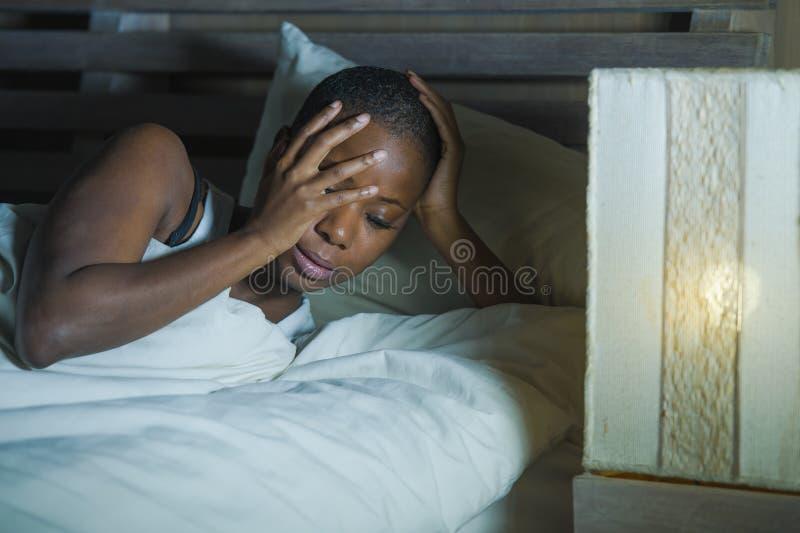 Lebensstilnachtporträt junger trauriger und betonter Schwarzafrikaner Amerikanerin, die auf dem Bettumkippen versucht, zu schlafe lizenzfreie stockfotos