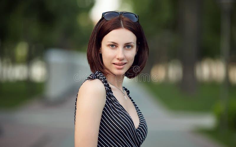 Lebensstilporträt bilden erwachsene entzückende frische schauende Brunettefrau ohne die Pendelfrisur, die den Abendpark aufwirft, stockfotografie