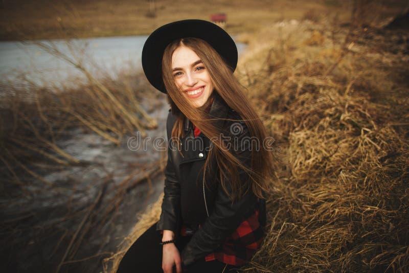 Lebensstilporträt der jungen Frau im schwarzen Hut, der durch den See an einem schönen und warmen Herbsttag stillsteht lizenzfreie stockfotografie