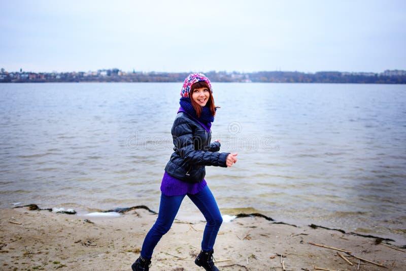Lebensstilporträt der jungen kaukasischen dünnen Frau läuft entlang Strandherbst stockfoto