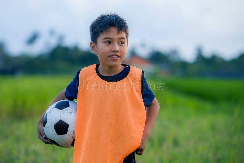 Lebensstilporträt des hübschen und glücklichen Jungen, der den Fußball draußen spielt Fußball an grüne Rasenfläche lächelndem che lizenzfreie stockfotografie