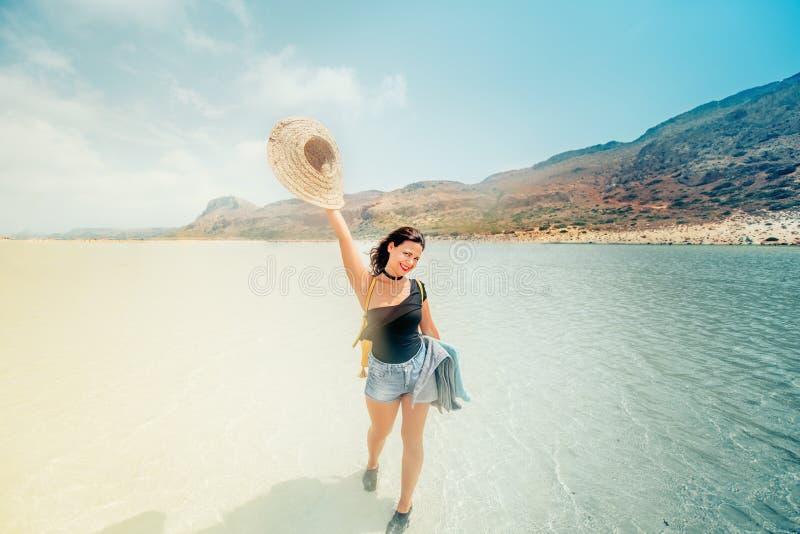 Lebensstilporträt des recht glücklichen Mädchens mit gebräuntem sexy Körper, tragender Strohhut, lächelnd und nehmen ein Sonnenba stockbilder