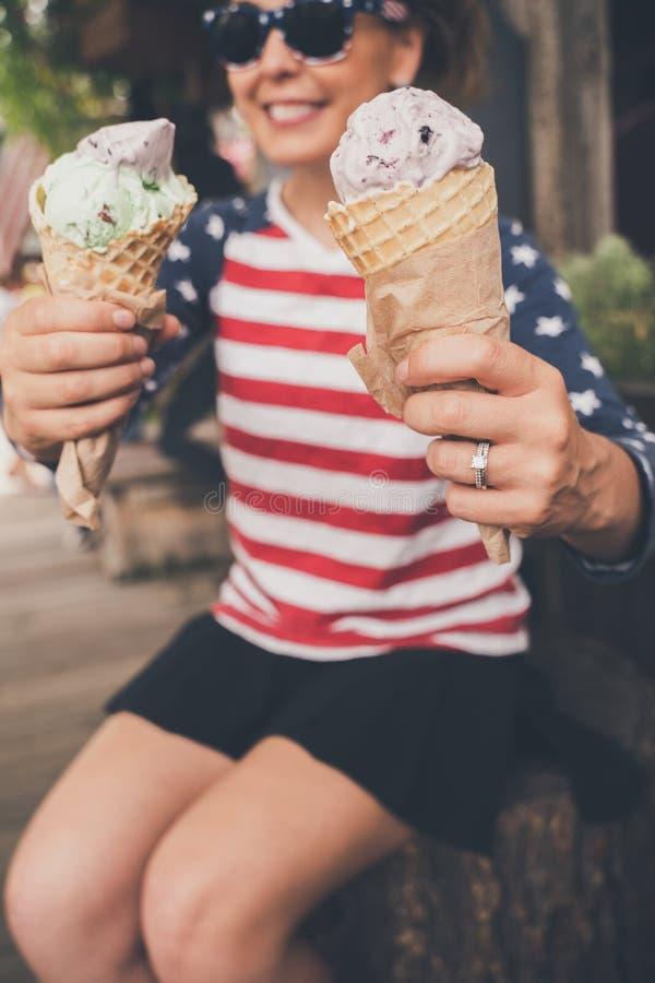 Lebensstilporträt einer jungen Frau, die Americana-Kleidung, einen Waffelkegel genießend trägt Fokus auf Eistüte, Frau lizenzfreie stockfotografie