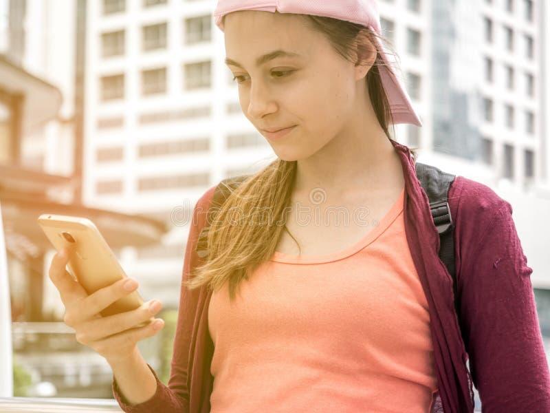 Lebensstilporträt eines jungen schönen Mädchentouristen-Stellungslächelns beim Haben des Spaßes und Betrachten von Handys stockfotografie