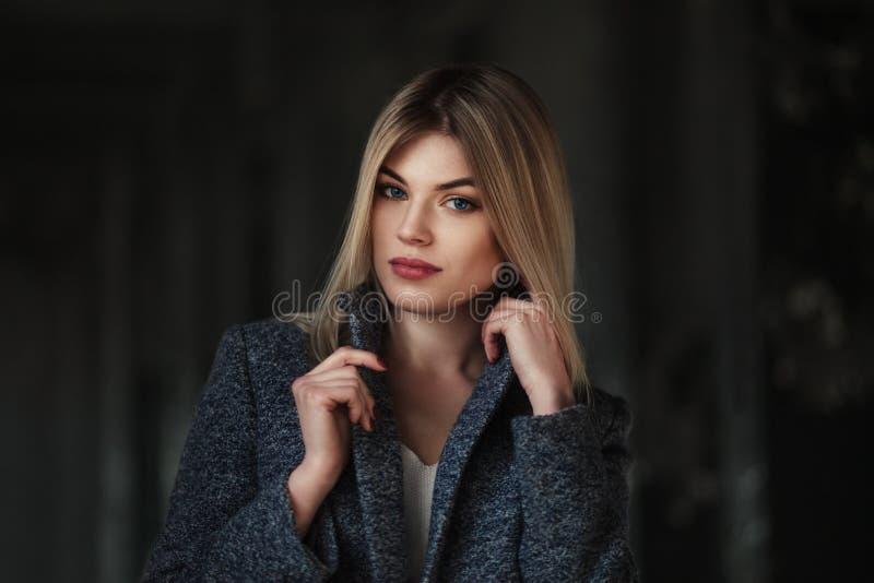 Lebensstilporträt im Freien der schönen blonden jungen Frau Aufstellung auf städtischem Hintergrund Art und Weisefoto stockbild