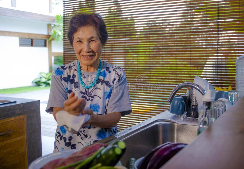 Lebensstilporträt von älterem glücklichem und süßem asiatischem japanischem im Ruhestand, Frau, welche zu Hause die Küche wäscht  lizenzfreie stockfotografie