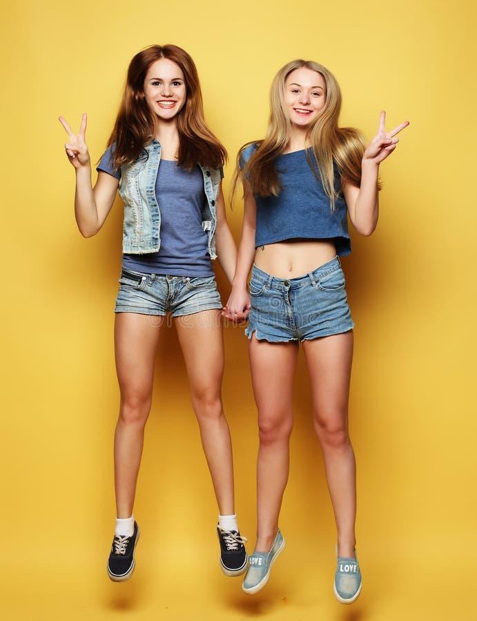 Lebensstilporträt von zwei besten Freunden der jungen Mädchen springen über YE stockfotografie