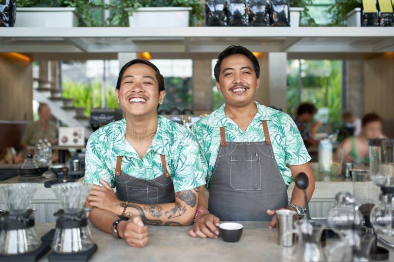 Lebensstilporträt von zwei freundlichen lächelnden Balinese tausendjährigen baristas, die modische Kleidung und Schutzbleche im H lizenzfreie stockbilder