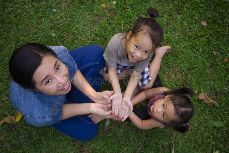 Lebensstilportr?t-Muttersohn und Tochter im Gl?ck an der Au?enseite in der Wiese, lustige asiatische Familie in einem gr?nen Park lizenzfreies stockfoto