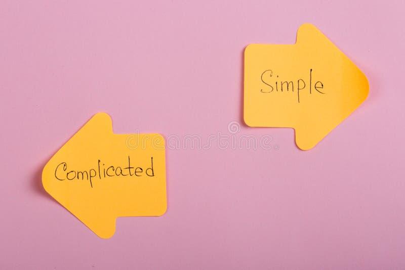 Lebenswahl - orangefarbene Aufkleber in Form von Indexpfeilen mit Text kompliziert und einfach auf rosa Hintergrund lizenzfreie stockbilder