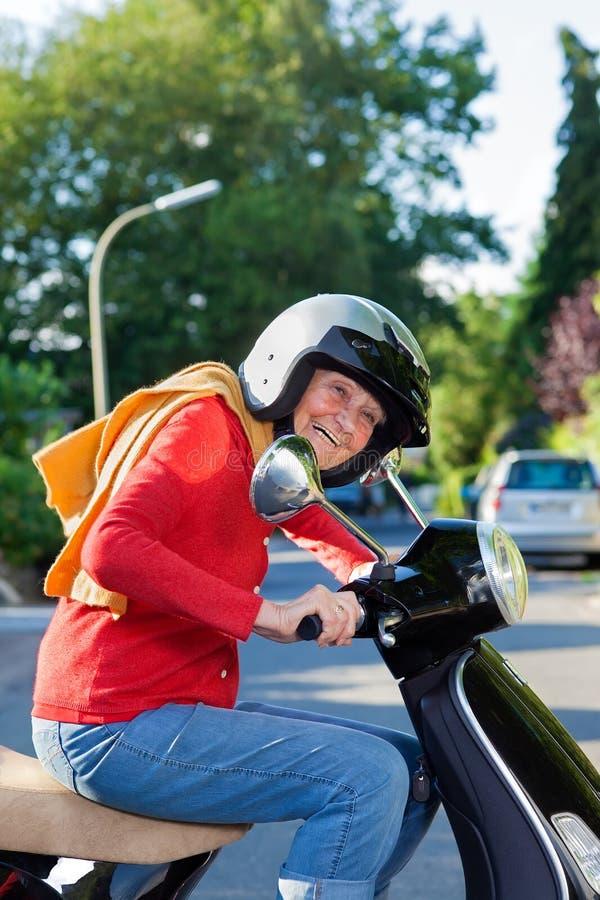 Lebhafte ältere Frau, die einen Roller reitet stockfotografie