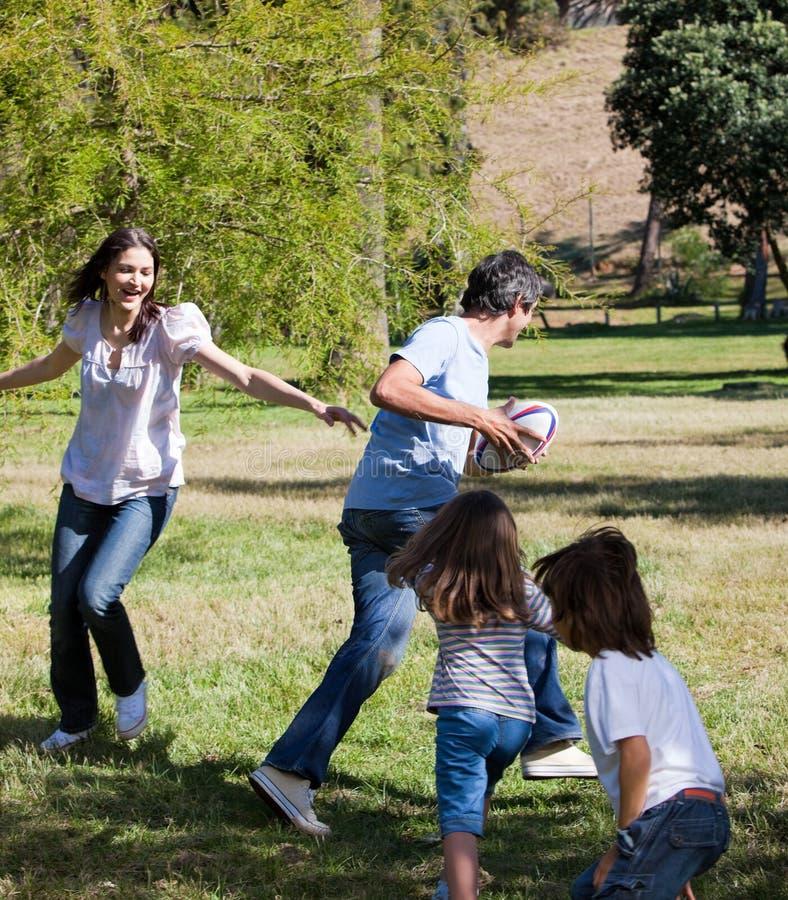 Lebhafte Familie, die Rugby spielt lizenzfreies stockfoto