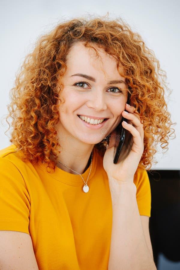 Lebhafte junge Frau mit locker roten Haaren, die am Telefon spricht lizenzfreie stockfotografie