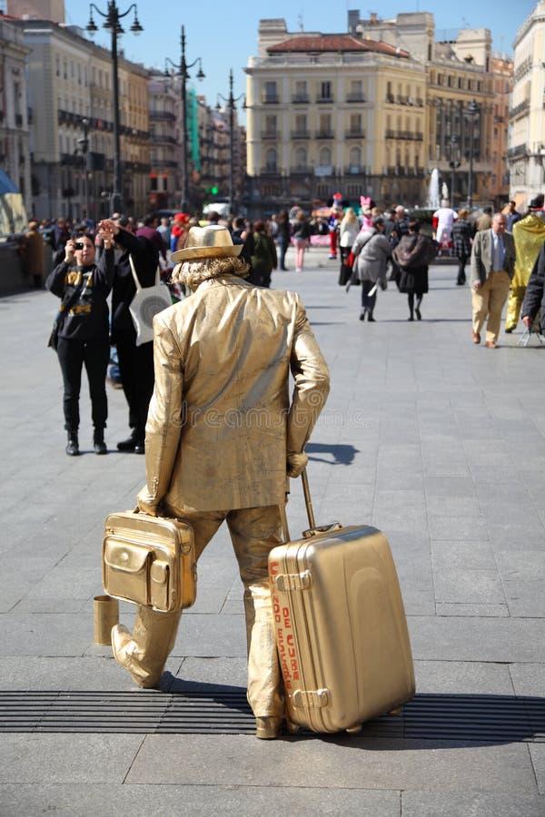 Lebhafte Skulptur - goldener Mann mit großer Tasche an der Straße stockbilder