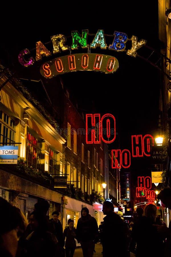 Lebhafte Szene auf Carnaby Street London mit der Lichterkette, die HO HO HO formuliert stockfoto