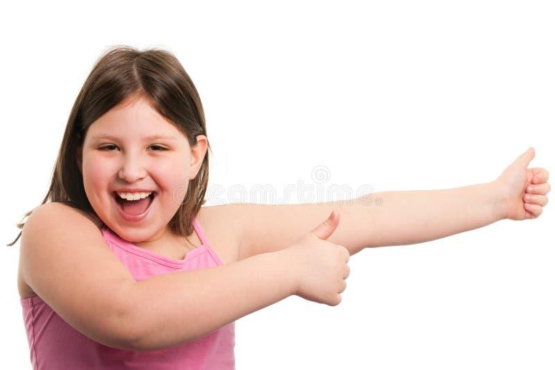 Lebhaftes lachendes Mädchen mit den Daumen oben lizenzfreie stockfotografie