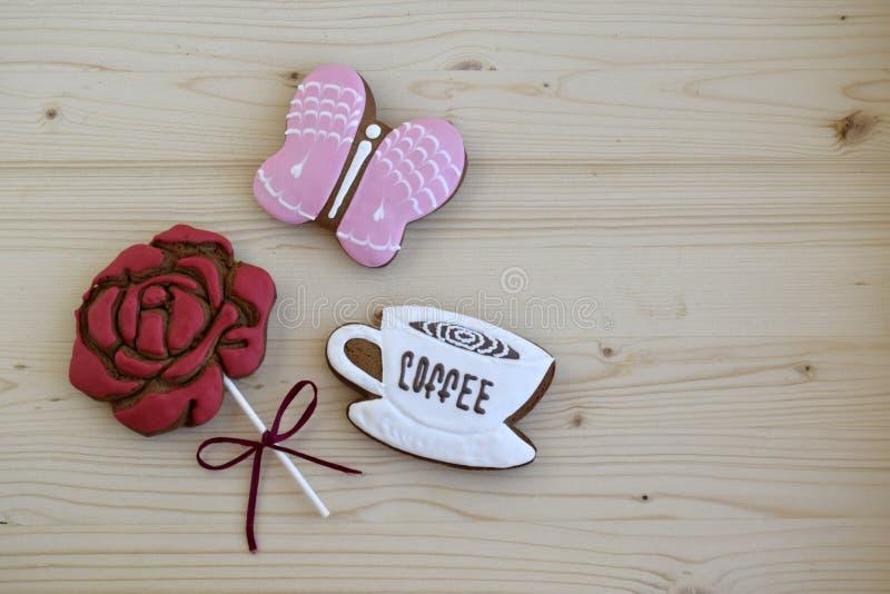 Lebkuchen in Form einer Schale mit Kaffee, einer rosafarbenen Blume und einem Schmetterling stockfoto