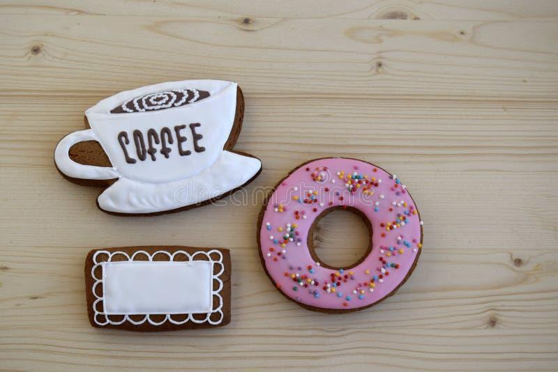 Lebkuchen in Form einer Schale mit Kaffee, einer Serviette und einem runden Bagel sind auf einem Holztisch lizenzfreie stockbilder