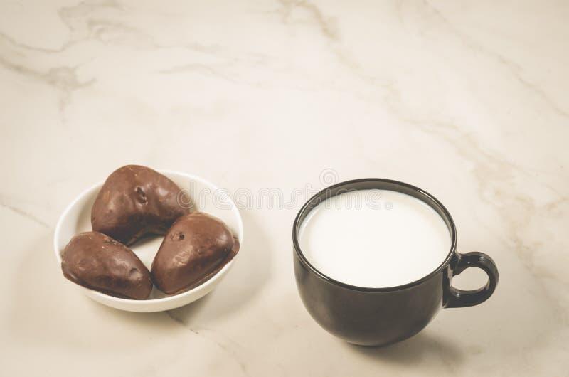 Lebkuchen in Form von Herz- und Milch-/Schokoladenlebkuchen und Milch in einem schwarzen Becher auf einem weißen Marmorhintergrun lizenzfreie stockfotos
