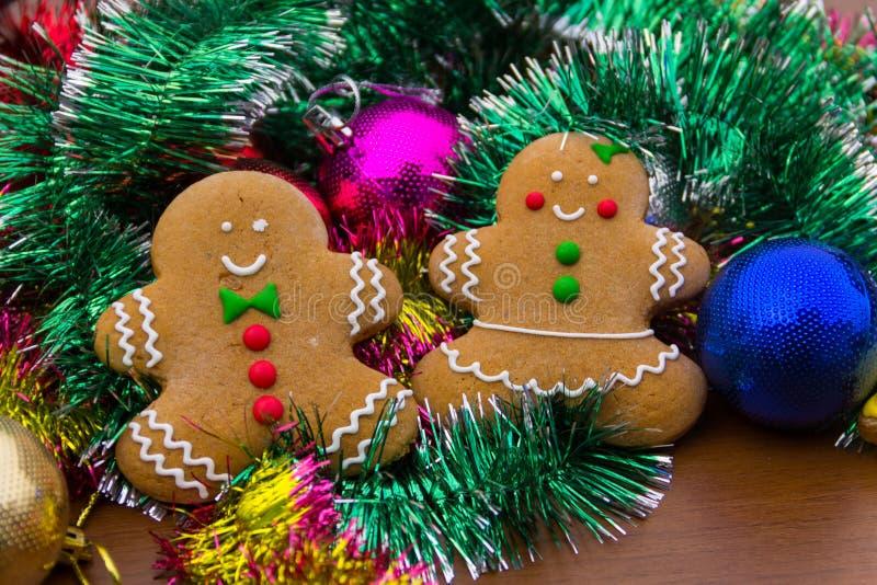 Lebkuchenmänner mit Weihnachtsbällen und -lametta lizenzfreie stockfotografie