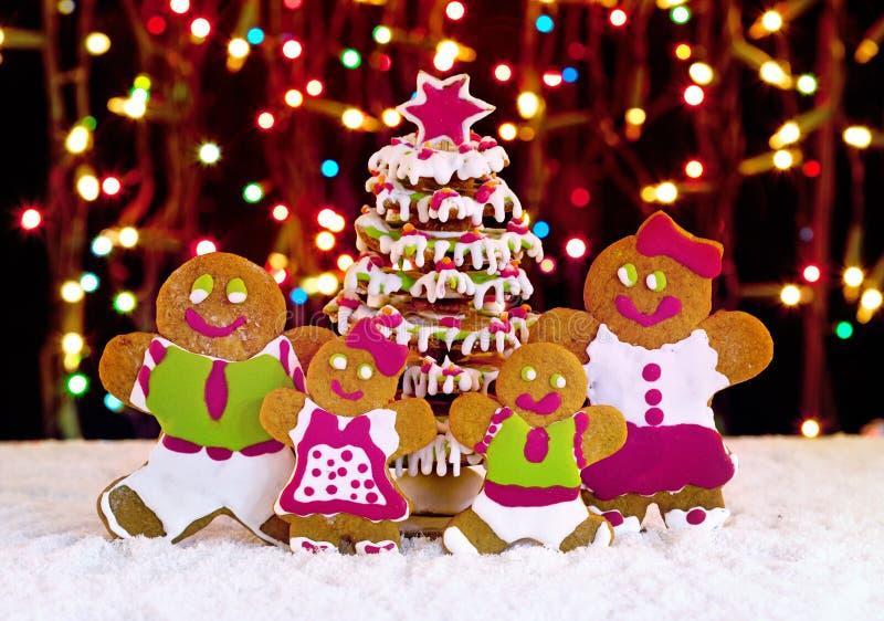 Lebkuchenplätzchenfamilie vor Weihnachtsbaum lizenzfreie stockfotos
