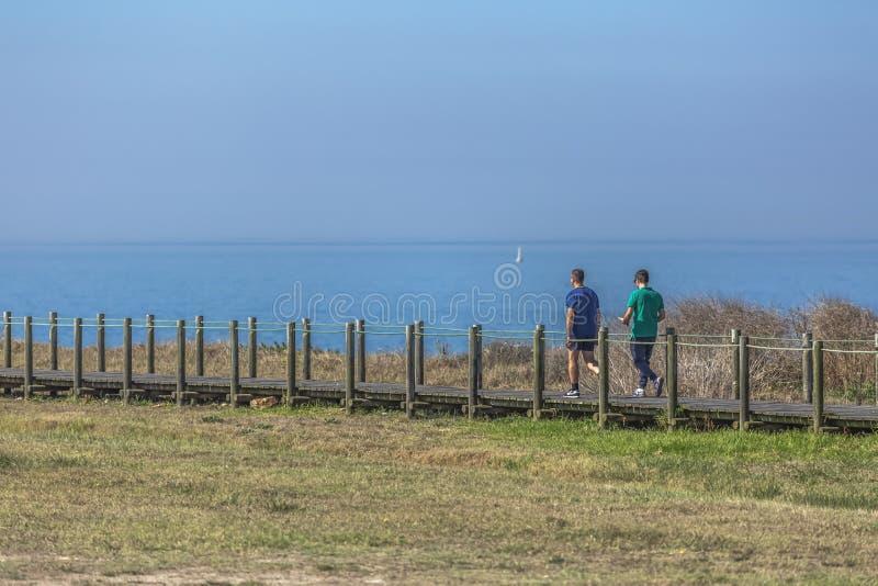 Leca da Palmeira/Порту/Португалия - 10 04 2018: Задний взгляд 2 людей, идя и говоря на пути eco пешеходном, около моря, стоковые изображения rf
