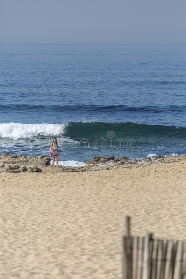 Leca da Palmeira/波尔图/葡萄牙- 10 04 2018年:波尔图/葡萄牙- 10 04 2018年:在一个女孩,单独,立场和看的看法在海滩  免版税库存图片