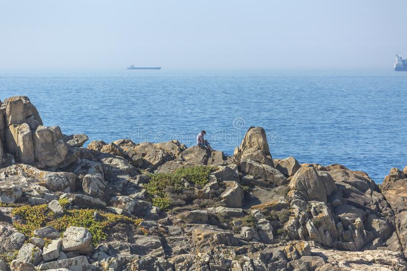 Man enjoying the view, sitting on the rocks, next to the beach of Leca da Palmeira, background with ocean and ships royalty free stock images