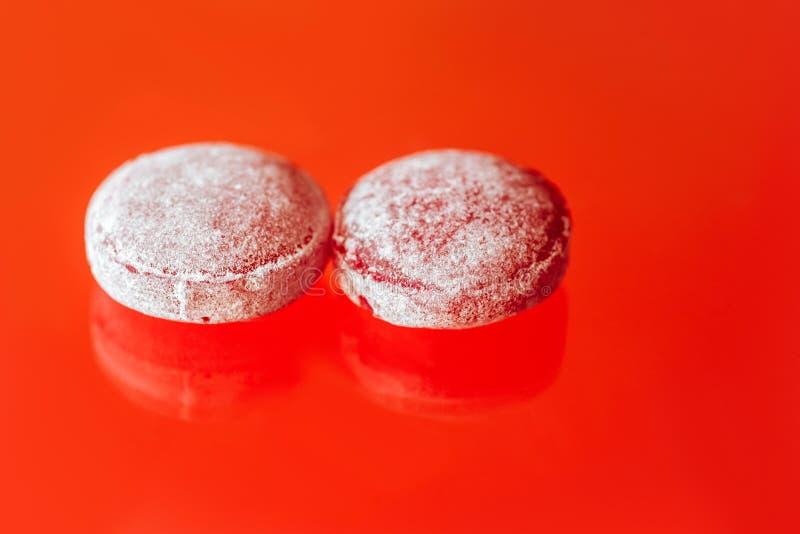 Lecca-lecca dolci spruzzate su un fondo rosso immagini stock libere da diritti