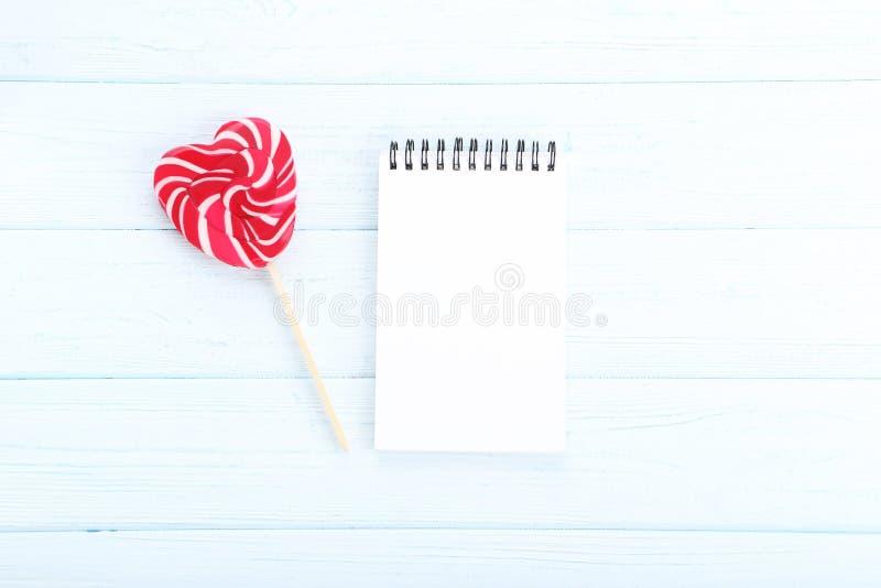 Lecca-lecca a forma di del cuore con il taccuino fotografia stock