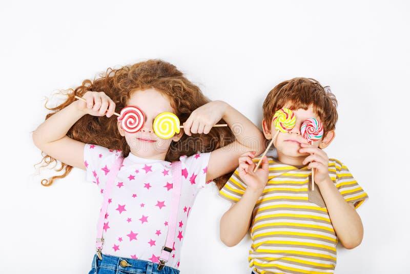 Lecca-lecca divertente della caramella della tenuta dei bambini fotografia stock libera da diritti