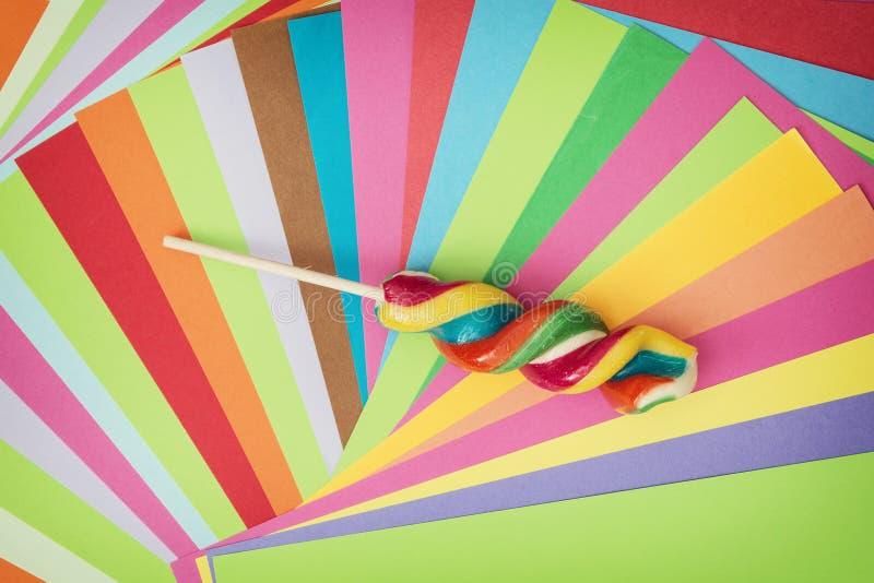 Lecca-lecca dolce torta variopinta e carte brillantemente colorate posteriori fotografie stock libere da diritti