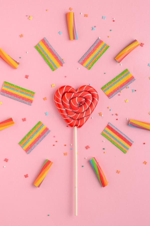 Lecca-lecca rossa nella forma di cuore e dei dolci variopinti su un fondo rosa, disposizione piana fotografia stock
