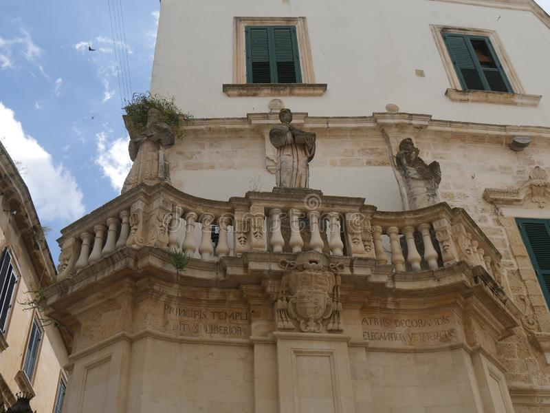 Lecce - Piazza Duomo propylaea. Propylaea in the entrance of Piazza Duomo are two opposite balconies in baroque style supporting the statues of  st Oronzo, Irene stock images