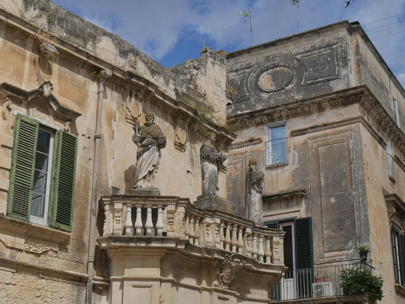 Lecce - Piazza Duomo propylaea. Propylaea in the entrance of Piazza Duomo are two opposite balconies in baroque style supporting the statues of  st Oronzo, Irene stock image