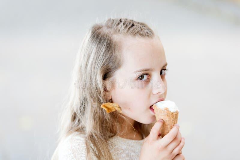 Lecchi il yogurt congelato Dente dolce della ragazza mangiare il gelato Bambino con il cono gelato a disposizione Gelato bianco d immagine stock