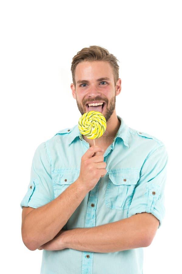 Lecchilo Tipo barbuto bello dell'uomo che sorride mentre leccando caramella Il sorriso allegro del tipo macho ritiene felice e so immagine stock
