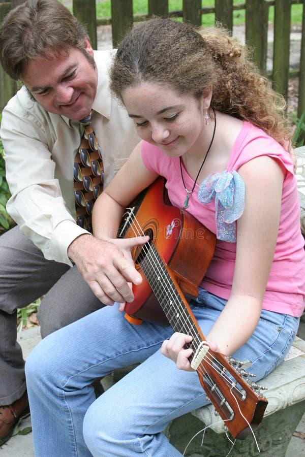 Lección 1 de la guitarra de la hija del padre foto de archivo