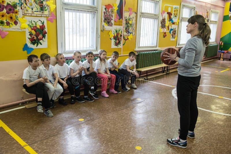 Lección de la educación física de los niños de grados elementales adentro fotos de archivo