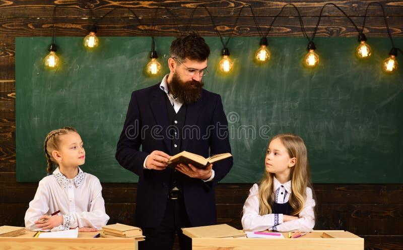 Lección de la escuela lección de la escuela de dos pequeñas muchachas niñas y profesor serio en la lección de la escuela Lección  imagen de archivo libre de regalías