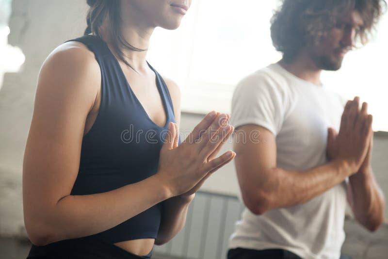 Lección de la yoga del gesto del namaste del hombre joven y de la mujer imagen de archivo libre de regalías