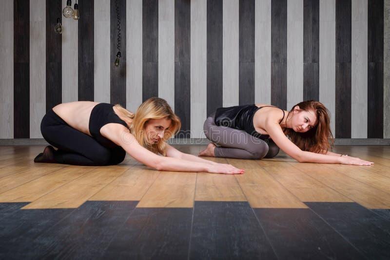 Lección de la yoga Instructor de sexo femenino hermoso joven que entrena al estudiante en yoga en club de fitness imagen de archivo