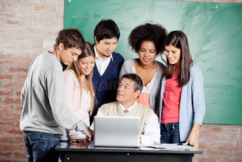 Lección de With Laptop Explaining del profesor a los estudiantes fotografía de archivo