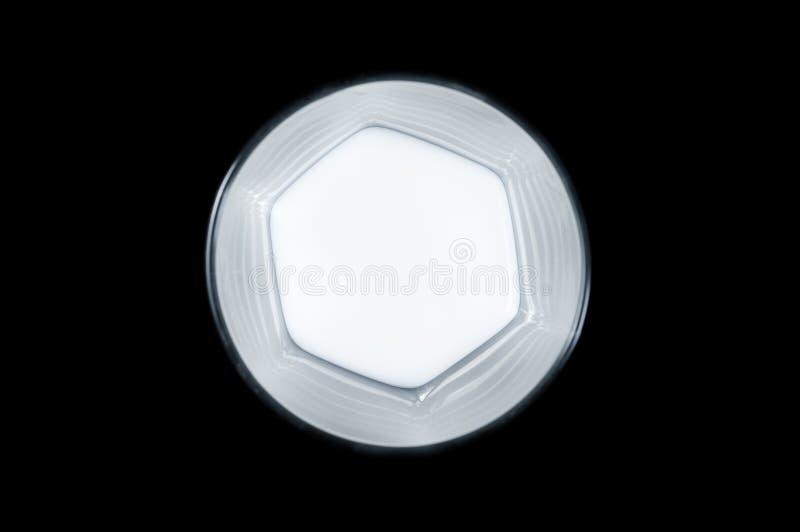 Leche blanca en una opinión superior de cristal de cristal transparente sobre un fondo negro, aislante fotos de archivo libres de regalías