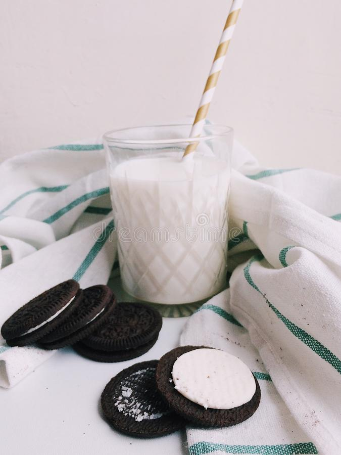 Leche con las galletas Oreo en el fondo blanco fotos de archivo