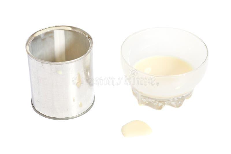 Leche condensada con el azúcar en bol de vidrio y lata fotografía de archivo