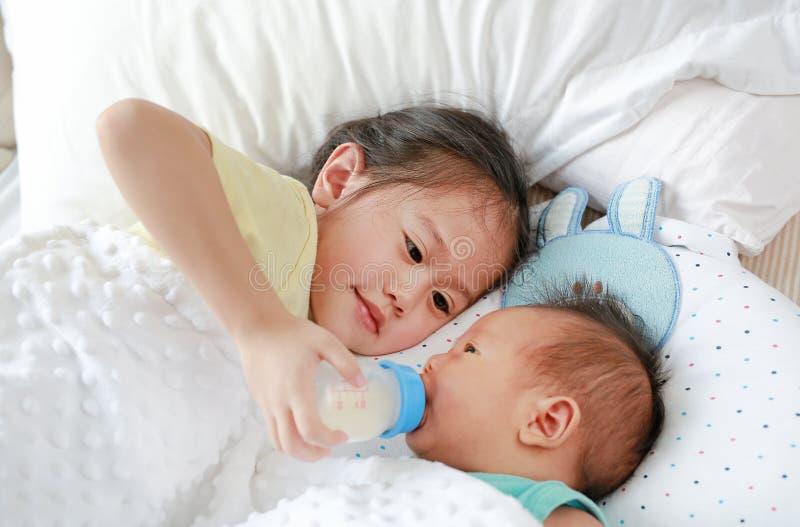 Leche de alimentación de la más vieja hermana asiática adorable de la botella para el bebé recién nacido que miente en la cama fotos de archivo